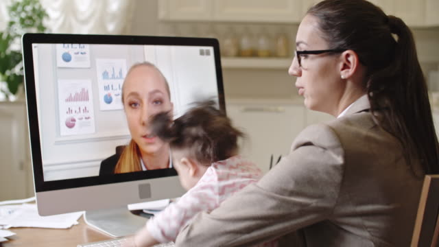 Young mother having video call with business partner video