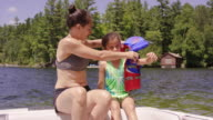 Young mother helping her daughter put lifejacket on in boat video