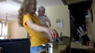 Young mother hold baby girl, prepare food in kitchen video