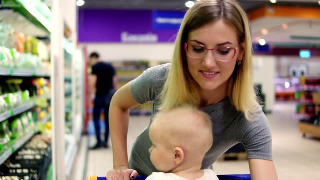 Young mother is choosing cabbage and other vegetables, while her little child is sitting in a grocery cart. Family shopping in the supermarket video