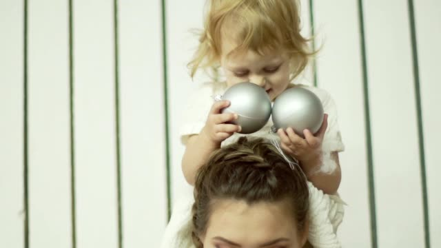 Young mother is playing with her little daugther. Little cute baby girl sits on her mother's shoulders video
