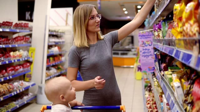 Young mother is reading product contents on the package of cookies and smiling while her little baby is sitting in a grocery cart in the supermarket video