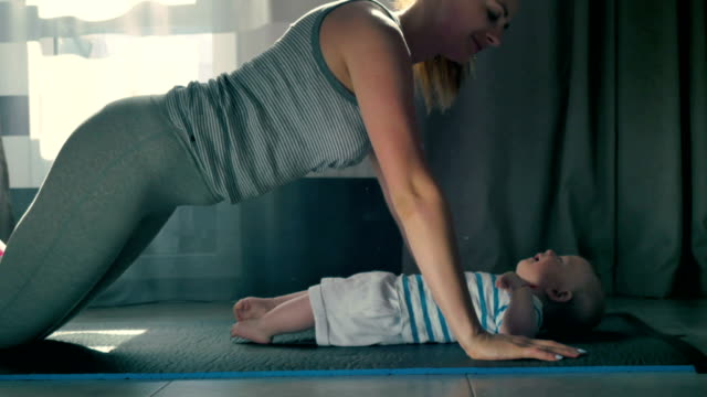 Young mother kiss her baby during doing a push ups from floor video