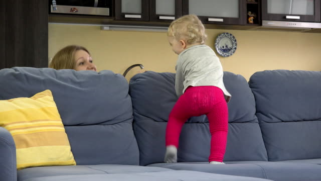 Young mother play hide and seek under sofa with her cute toddler daughter. video