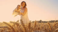 Young mother playing with her baby in wheat field video
