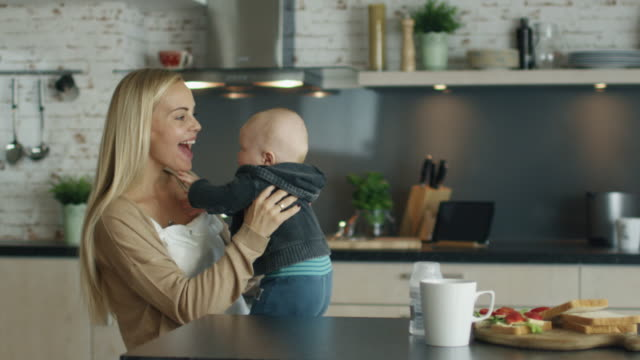 Young Mother Plays with Her Beautiful Baby while Standing on the Kitchen. In Slow Motion. video