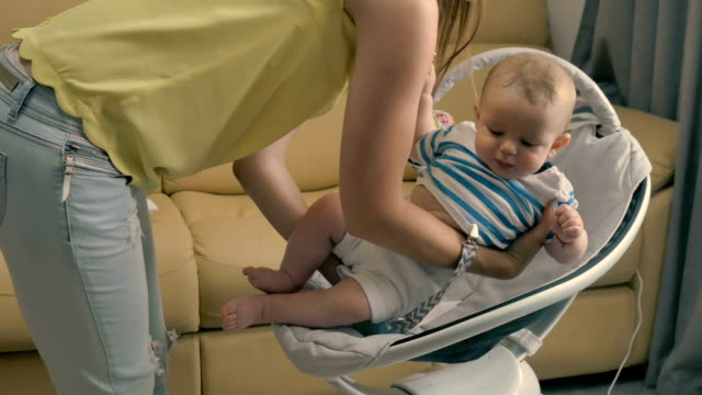 Young mother puts her little son into the cradle video