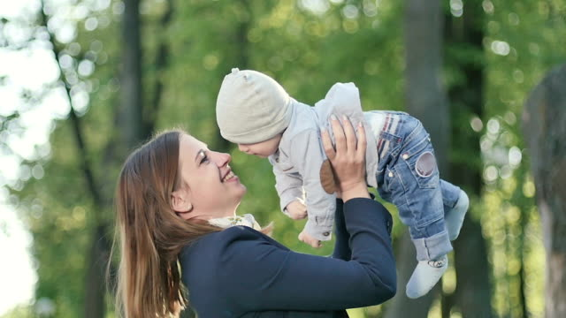 Young mother rejoice with little son in park video