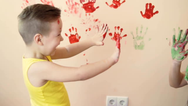 Young mother with her little boy are lmixing colors at their hands yo leave beautiful handprints on the wall. Mother and child concept. Slowmotion. video
