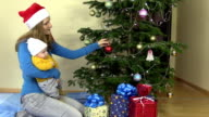 young mother with infant baby in hands hang Christmas tree toy video