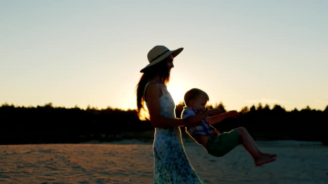Young mother with long hair playing with his son at sunset. Fun turns it around video