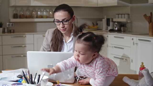 Young mother working on laptop in kitchen video