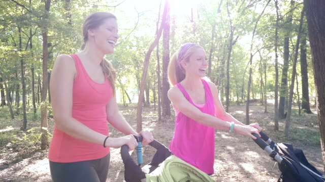 Young mothers exercising together in park, pushing toddlers in strollers video