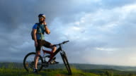 4К Young mountain biker talking on phone on top video