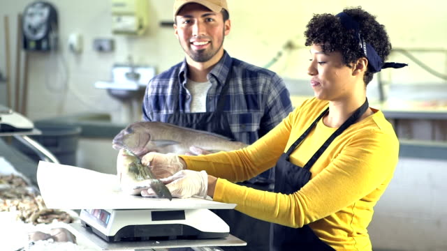 Young multi-ethnic couple working in fish market video