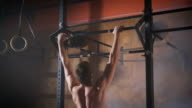 Young muscular athlete doing pull-up exercises video