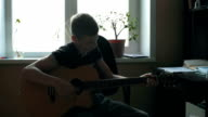 Young Musician Playing Solo On Classic Guitar, Finger style Close Up. An acoustic guitar uses only acoustic means to transmit the strings' vibration energy to the air in order to make a sound. video
