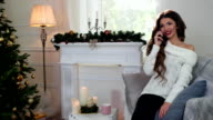 young nice girl speaks by mobile phone in sitting in the living room on a sofa near Christmas tree, Winter weekend during Christmas Eve video