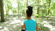 Young off road runner jogging on dirt path in sunny wooded park video