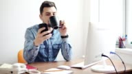 Young office worker using his phone at the office sitting at the table with computer, phone and drinking coffee or tea from his cup. Shot in 4k video