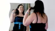 young overweight woman is trying a dresses in front of the mirror video