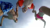 SLOW MOTION: Young parents jumping into pool with their son video