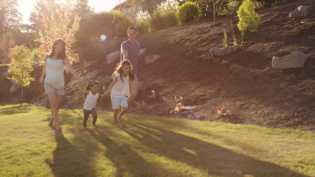 Young parents playing with their daughters in the backyard video