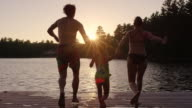 Young parents with daughter running and jumping off dock into lake video