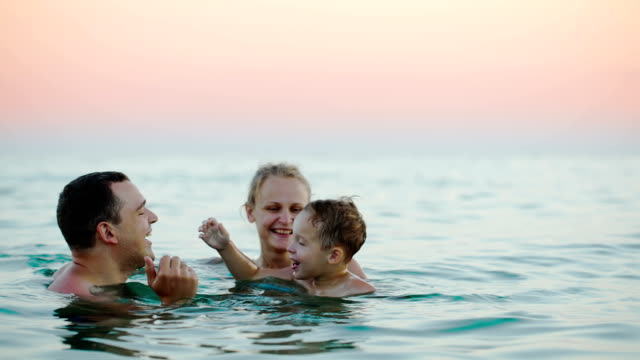 Young parents with son bathing in sea video