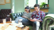 Young people browsing their smart phone in coffee shop. video