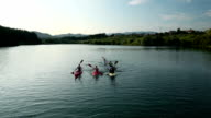 HD CRANE: Young people canoeing in the lake towards camera video