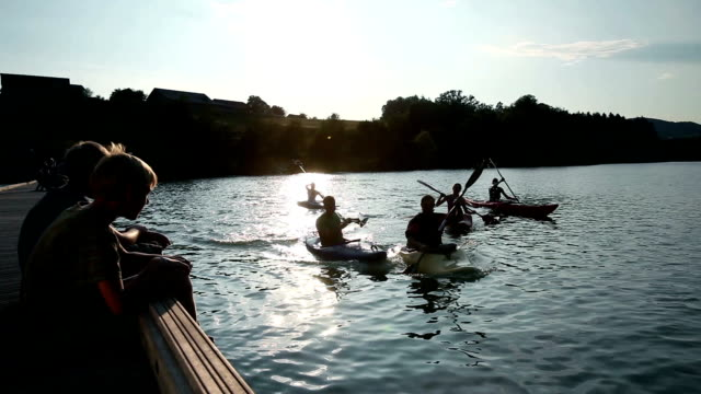 HD CRANE: Young people canoeing, two children watching at sunset video