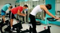 Young people doing sports exercises on the exercise bike in the gym video