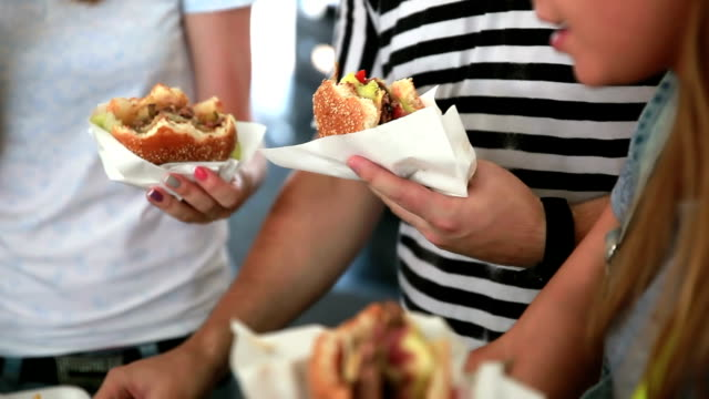 Young people eat burgers and fries on the street video