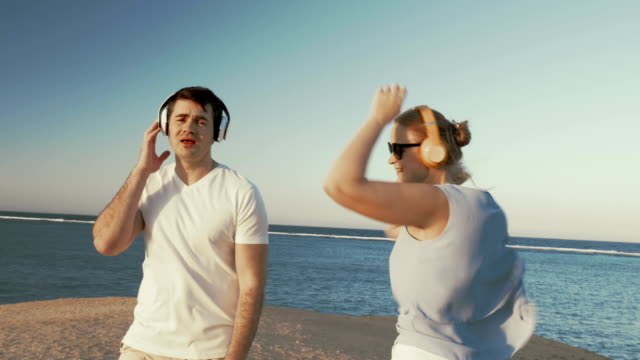 Young people in headphones relaxing on beach video