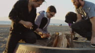Young People Lighting a Beach Bonfire video