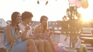 Young people on rooftop party, eating watermelon video