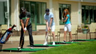 Young people play golf near the clubhouse video