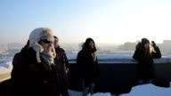 Young people playing snowball game on the roof of a high building video