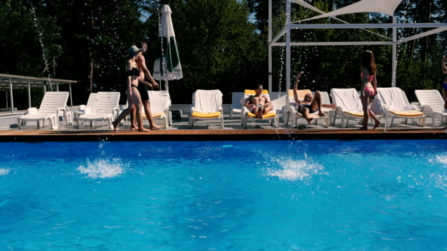 Young people relax near the swimming pool video