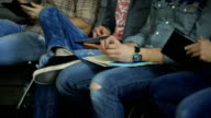 Young people sitting in a row, keep on their laps notebooks, smartphones and tablets video
