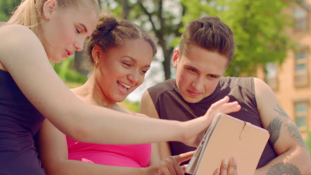 Young people watching photo on tablet outdoor. Young friends having fun video