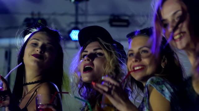 young People with bright drinks at nightclub, nightlife, happy women drinking during dancing at night party, cocktail party video
