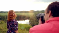 Young photographer takes photo of young red-haired woman at summer outdoor on nature video