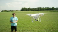 SLOW MOTION: Young pilot flying hobby drone on a field video