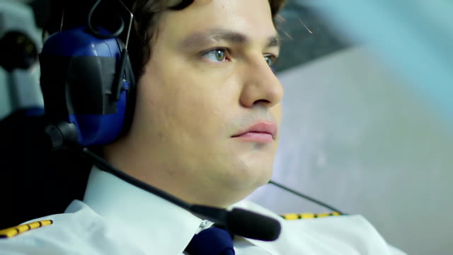 Young pilot steering airplane and pushing buttons on flight panel, profession video