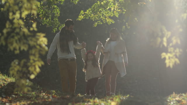 Young playful parents having fun with daughter in autumn park. video
