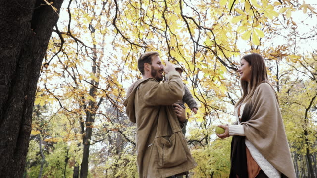 Young playful parents having fun with their small son in autumn park. video