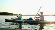 Young positive couple paddling kayak at sunset, beautiful view video