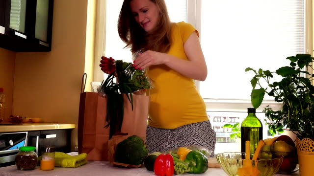 Young pregnant wife unload natural vegetables from shopping bag on kitchen table video